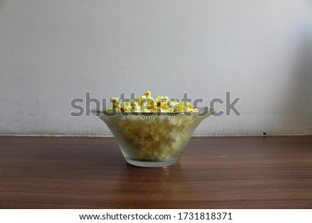 Eye view angle photo of a glass bowl having floral print full of yellow popcorn, kept on a brown wooden table with white background at home. Selective focus on popcorn, background blur. #1731818371