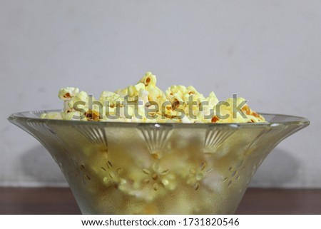 Eye view angle photo of a glass bowl having floral print full of yellow popcorn, kept on a brown wooden table with white background at home. Selective focus on popcorn, background blur #1731820546
