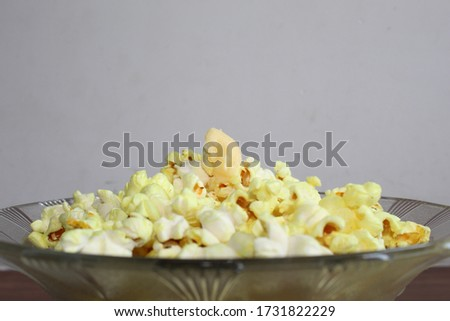 Eye view angle closeup photo of a designer glass bowl full of yellow popcorn with butter on it, kept on a brown wooden table with white background at home. Selective focus on butter, background blur.  #1731822229
