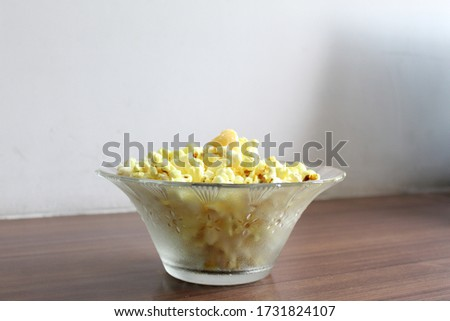 High angle photo of a glass bowl having floral print full of yellow popcorn with butter on it, kept on a brown wooden table with white background at home. Selective focus on popcorn, background blur.  #1731824107