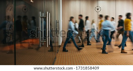 Group of office employees in motion go around at coworking space. People in business center walking  at hall. Motion blur. Wide image
