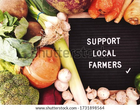Support local farmers sign against a rustic background of fresh vegetables, eggs and produce. Farming and agriculture. Locally sourced, organic and healthy veggies.