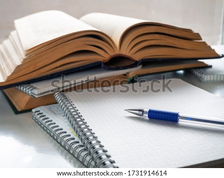 The pen lies on a blank sheet of notebook. Nearby open books and notebooks. Study, scientific work, abstract, study of literature. Background with books, notebooks and pen. Royalty-Free Stock Photo #1731914614