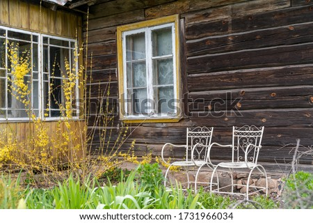 Nice looking entrance to the homestead like farm building. Amazing garden in front of the cabin. Old looking vintage chairs and benches in terrace area. Log cabin with traditional architecture.Estonia