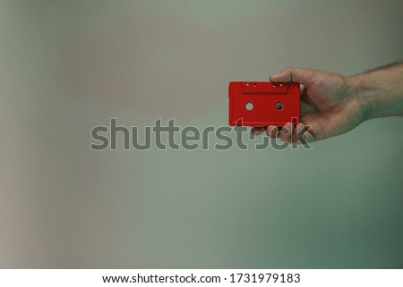 Hand holding red audio cassette tape in the color light. Beautiful minimal in neon light. Minimalism retro style concept. Background pattern for design.