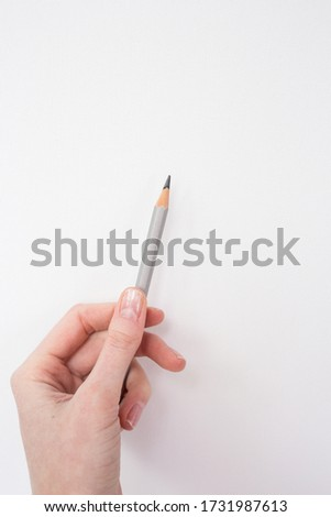 One gray pensil on the hand in the white canvas background. Drawing by pencils. Hobby during quarantine. Inspiration, talent. Creating a new picture, sketch. An artist. Art.
