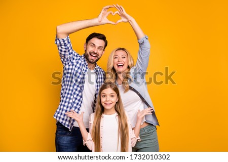 Photo beautiful mom lady handsome dad little school girl daughter showing happy parents celebrate anniversary make heart figure wear casual clothes isolated yellow color background