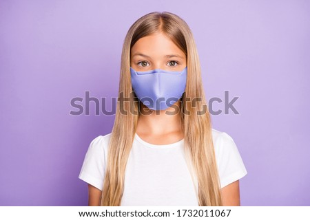 Close up photo of pretty positive cheerful child look have covid-19 quarantine her family friends wear white breathing mask t-shirt clothes isolated over violet color background #1732011067