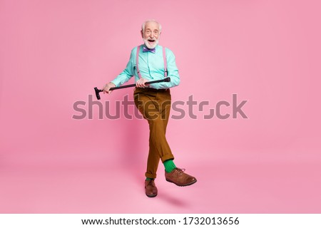 Full length photo of active grandpa moving dance pensioner party use walk stick raise leg wear mint shirt suspenders bow tie pants shoes green socks isolated pink pastel background #1732013656