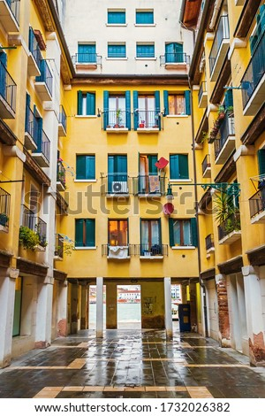 Old Italian residential house in Italia.Beautiful architecture in Venice.House painted in yellow paint with green wooden window shutters on island near Venezia.Popular travel destination in Europe #1732026382