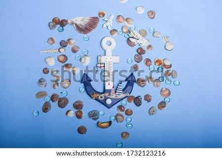 Decorative anchor on seashells and water drops background. Sea. Seashells on blue background.  Anchor thermometer. Abstract sea mood picture.