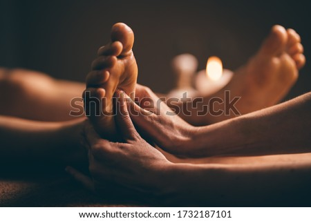 Professional foot massage close up. Authentic shot of luxury spa treatment. Charming light. Shallow depth of field. Stylized and colored. Royalty-Free Stock Photo #1732187101