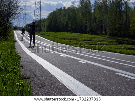 Training an athlete on the roller skaters. Biathlon ride on the roller skis with ski poles, in the helmet. Spring workout.Roller sport. Adult man riding on skates. #1732237813