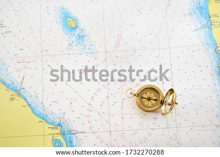 Retro styled golden compass (sundial) and old white nautical chart close-up. Vintage still life. Sailing accessories. Travel and navigation theme Royalty-Free Stock Photo #1732270288
