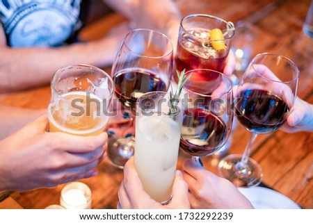 People toasting (cheers) with their drinks at a restaurant or bar #1732292239
