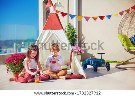 cute kids playing toys on summer patio, drinking fresh lemonade #1732327912