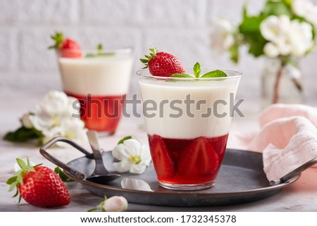Layered dessert in glass with vanilla panna cotta and jelly with strawberries Royalty-Free Stock Photo #1732345378