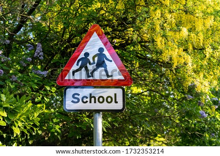school sign in London, UK.  Warning to slow down road sign with trees in the background