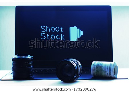 photo lenses and dollars on the background of the image with the text Shoot Stock on the laptop in the background