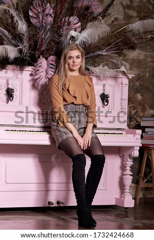 young girl  sits on a pink piano. Beauty portrait of a blonde in a shorts  an old brick wall