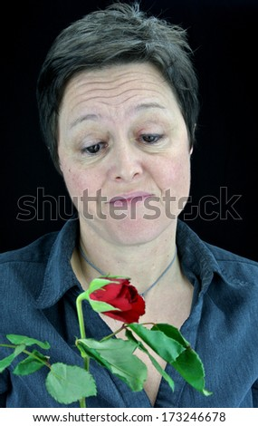 An unwanted valentine. Isolated portrait of an unimpressed woman holding a withering rose. #173246678