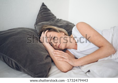 Depressed woman tormented by restless sleep, she is exhausted and suffering from insomnia, bad dreams or nightmares, psychological problems. Inconvenient uncomfortable bed or mattress. Lack of sleep #1732479443