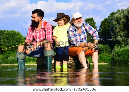 I love fishing. Fishing in river. Happy grandfather and grandson are fishing on the river. Three generations ages: grandfather, father and young teenager son #1732495586