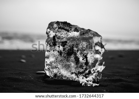 Piece of glacier covered with black soil lying on black sand beach against Atlantic Ocean in Iceland #1732644317