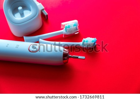 Modern white sonic or electric toothbrush set with replacement heads on flat lay background. Concept of professional oral care and healthy teeth by using sonic toothbrush