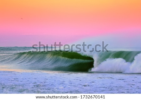 Sunset Perfection, an image of a wave breaking during sunset in Japan the wave is a perfect right hand barrel wave and the sunset is after a typhoon with stunning pinks and purples and hints of orange Royalty-Free Stock Photo #1732670141