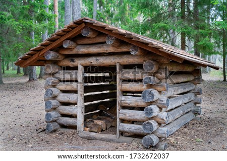 Small hut in the deep woods. Log cabin, rescue hut. Timber construction in the forest. Toiler, WC in the forest near the hiking trail. Shack for firewood. Homestead small hut. Amazing small log cabin #1732672037