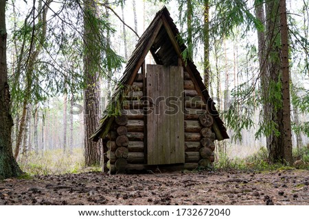Small hut in the deep woods. Log cabin, rescue hut. Timber construction in the forest. Toiler, WC in the forest near the hiking trail. Shack for firewood. Homestead small hut. Amazing small log cabin #1732672040
