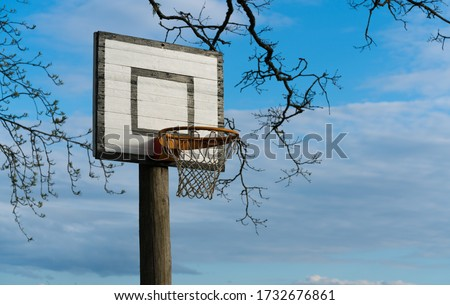Home made basketball field in the yard. Amazing sky on the background. Sports field. Basketball hoop and net. Nobody on image. Ball games - hobbies. Sporting equipment at home. Basket outside. Quality
