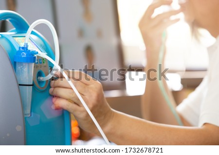 Middle Age man has respiratory problem from covid-19 so wear Inhaler Oxygen mask all time for treatment. Elderly Senior Boss meeting on Internet, adjust Air Quantity of Oxygen Concentrator Portable Royalty-Free Stock Photo #1732678721