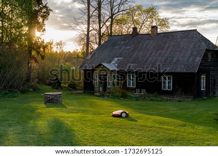 Amazing sunset picture of a farm with gorgeous garden. Self driving law mower taking care of amazing garden. Old restored traditional farm homestead. Summer sunset vibes all over it. Perfect sunset