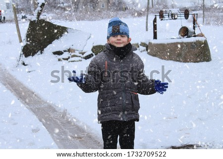 A little boy is standing in the snow and it is snowing.