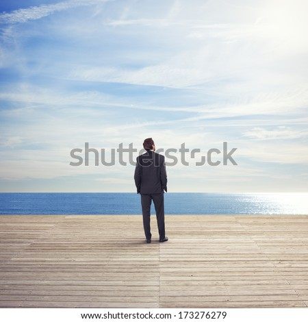 Business man standing on a pier looks the sea #173276279
