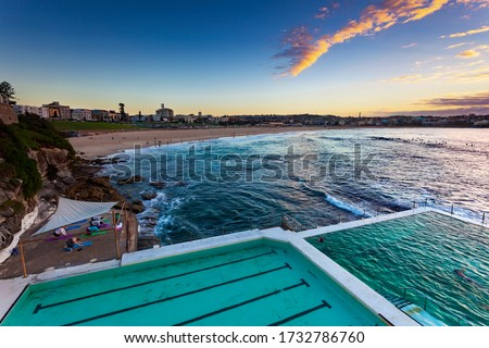 Sunrise over Bondi Beach showing people doing early morning yoga, exercise, swimming and surfing with turquoise waters, blue skies and clouds catching the sun's rays  #1732786760