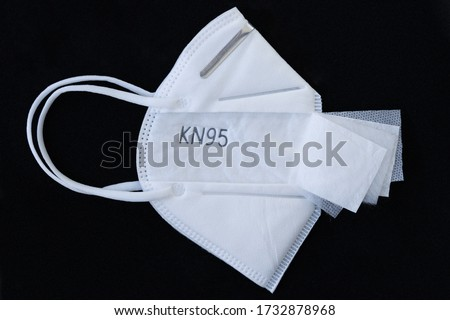 5 layer shear white KN95 FPP2 antivirus medical mask for protection against coronavirus on a black background. Doctor mask prevention of the spread of virus and pandemic COVID-19.