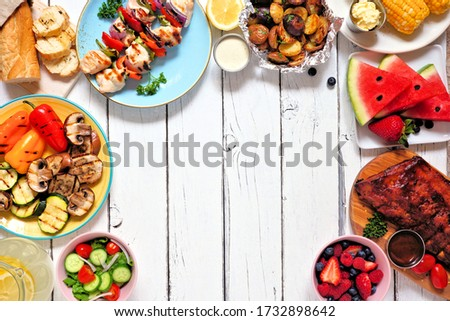 Summer BBQ or picnic food frame. Variety of grilled meats, vegetables, fruits, salad and potatoes. Above view over a white wood background. Copy space.