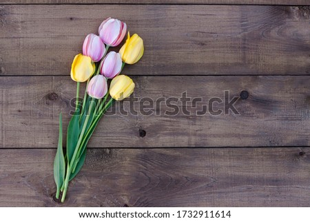 Pink and yellow tulips on a dark wooden background. Bouquet of fresh flowers. Top view #1732911614