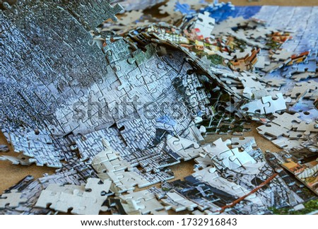 Pieces of the picture from the puzzles are scattered in a mess.
