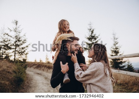 Stylish young family in the autumn mountains. A guy and a girl together with their daughter, are standing and hugging on the road against the background of a fence, forest and mountain peaks at sunset