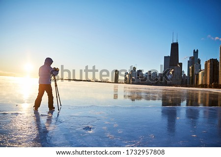 A view from the frozen lakefront of the beautiful downtown Chicago skyline during a subzero winter morning sunrise as a photographer composes a picture