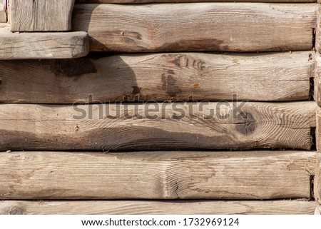 Old wooden wall of horizontal logs, texture. Photo background.Textile. The wall of the hunter's house