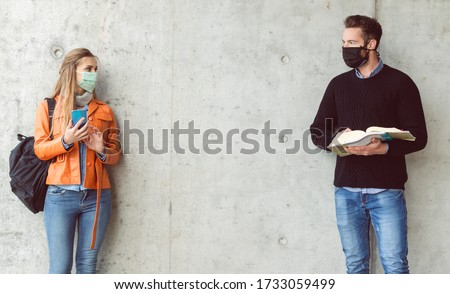Two students standing in social distance wearing face mask looking at each other #1733059499