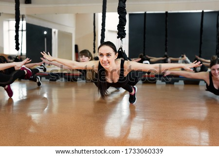 Close-up group of girls hanging on bungee rubber bands in the gym. Girls perform a difficult exercise with bungee gum #1733060339