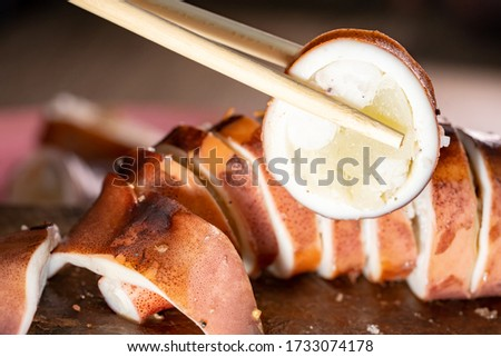 Grilled squid slice for cooking and eating in party night time, some boiling slice squid on chopsticks holding show delicious and tasty squid seafood, clos up view ring in resturant for people