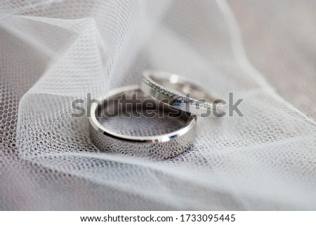 Macro picture of the two new beautiful elegant gold wedding ring's pair, one is plain, one is with small shiny diamonds, placed on the white bridal veil background