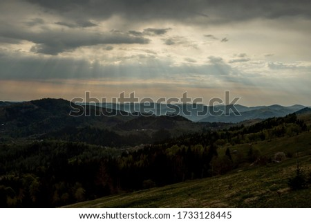 Beautiful sunset colors over the mountains of Carpathian, Ukraine, Europe. Sun setting after hot summer day. Photo in orange and blue natural tones #1733128445